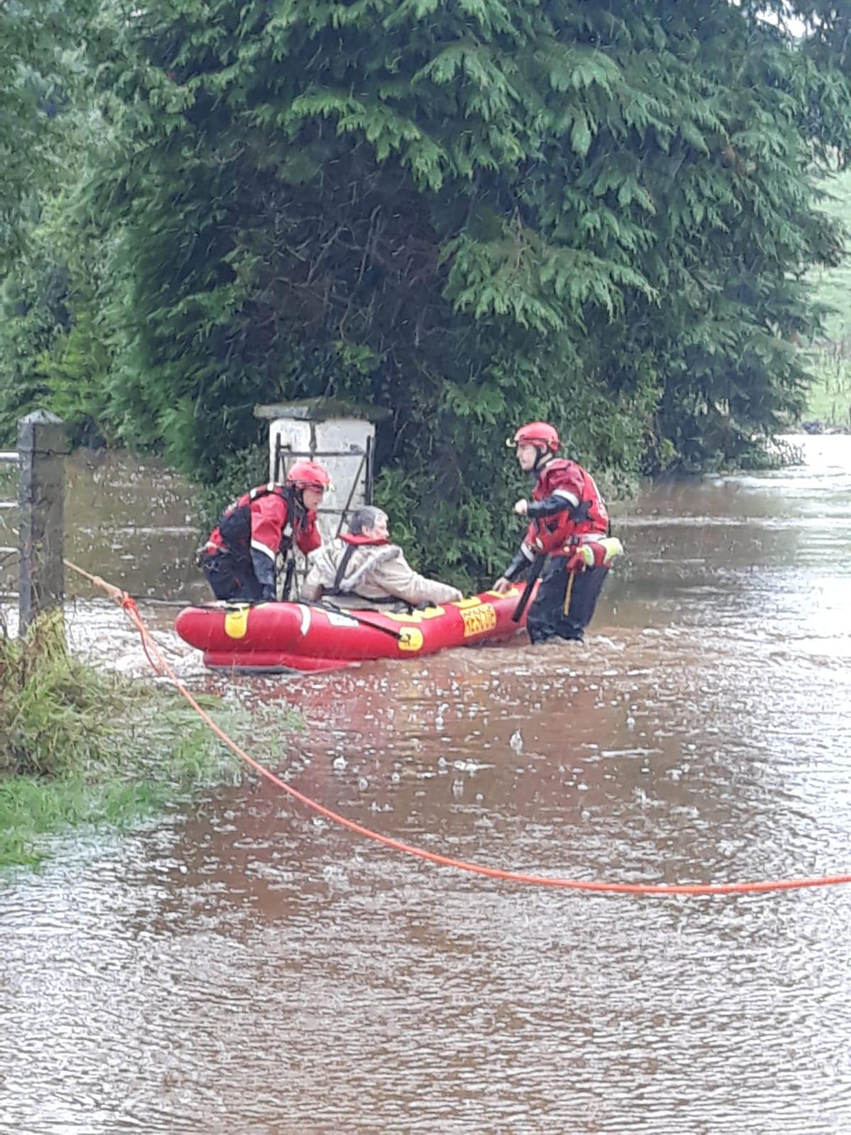 Two NIFRS responders helping an elderly women through flood