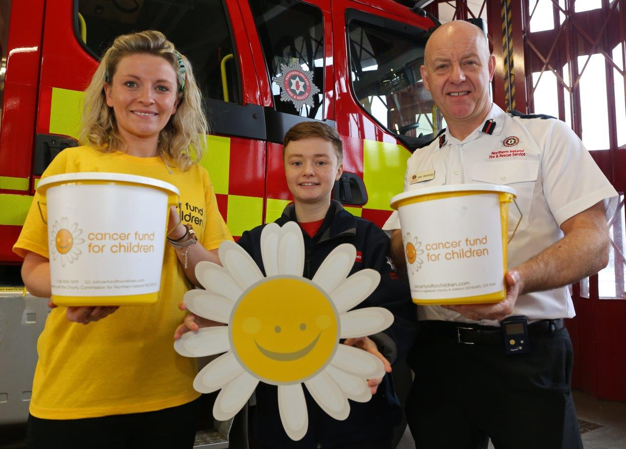 FireFighter posing with representitive from cancer fund and a child