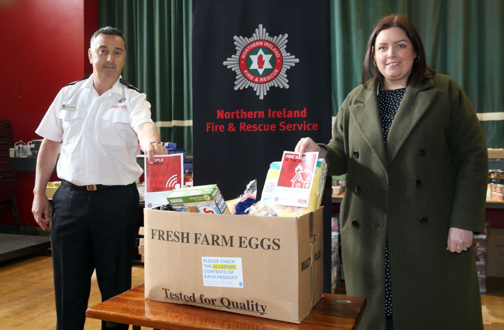 Paddy Gallagher & Deirdre Hargey beside food parcel