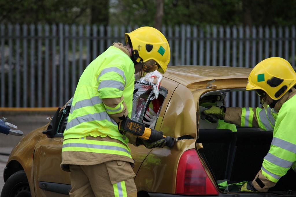 Firefighter cutting through car with powertool
